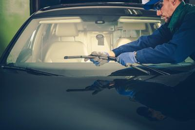 Reinstalling the windshield wipers after a windshield repair.